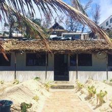 Our cottage on the beach in Tofo, Mozambique after the tropical storm went through there! Lost a bit of it's glam, but it's still standing! Emelia our amazing housekeeper is hard at work looking for the lawn and her flowers #praiadetofo #tofo #mozambique
