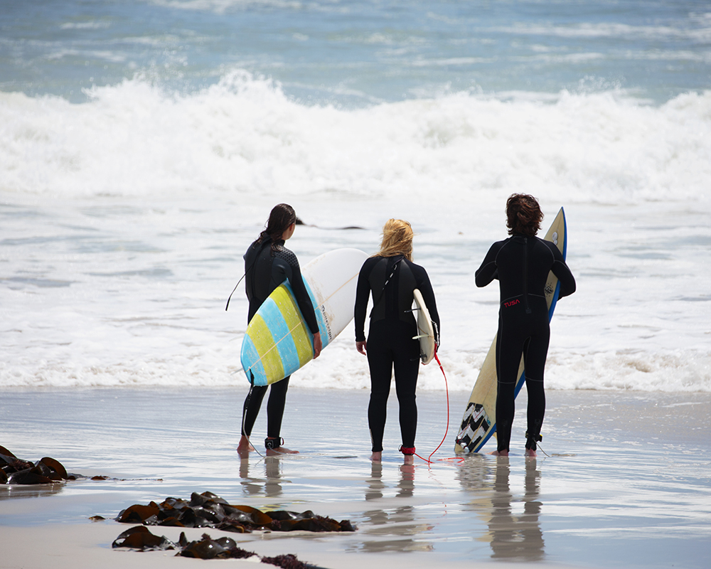 three surfers checking the waves